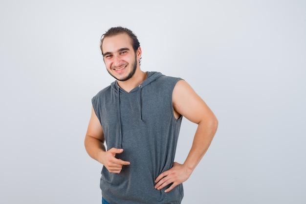 Junger passender mann, der mit hand auf taille im ärmellosen kapuzenpulli aufwirft und fröhlich aussieht. vorderansicht.