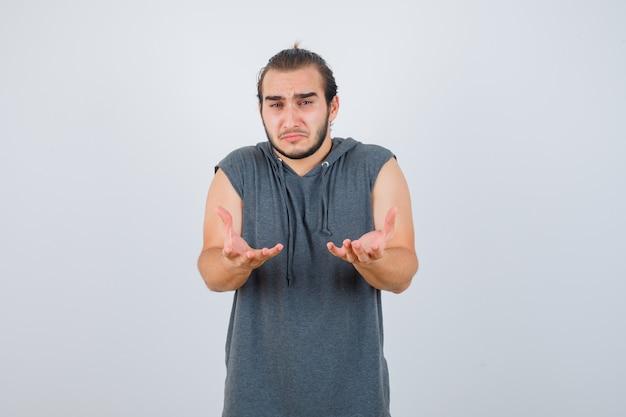Junger passender mann im ärmellosen kapuzenpulli, der hilflose geste zeigt und mürrisch sieht, vorderansicht.