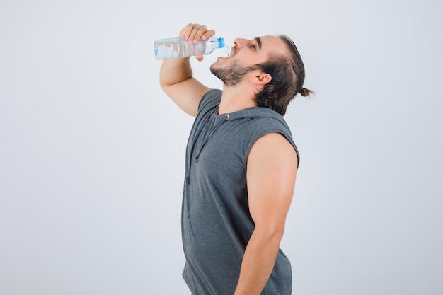 Junger passender mann im ärmellosen kapuzenpulli-trinkwasser und schaut fröhlich, vorderansicht.