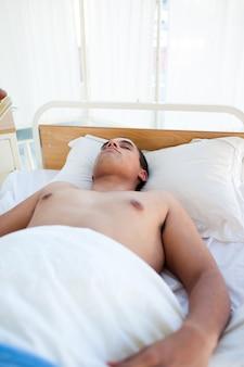 Junger patient, der auf einem krankenhausbett liegt