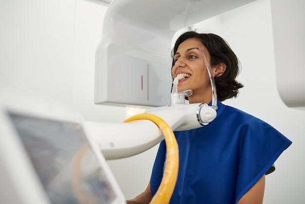 Junger patient, der auf röntgengerät steht. panorama-röntgen