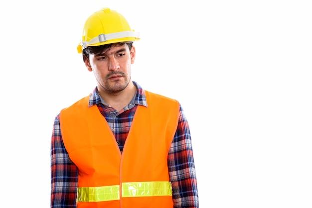 Junger persischer bauarbeiter, der denkt, während er traurig schaut
