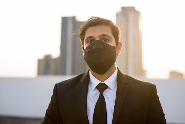 Junger persischer geschäftsmann, der maske zum schutz vor ausbruch und verschmutzung des koronavirus trägt