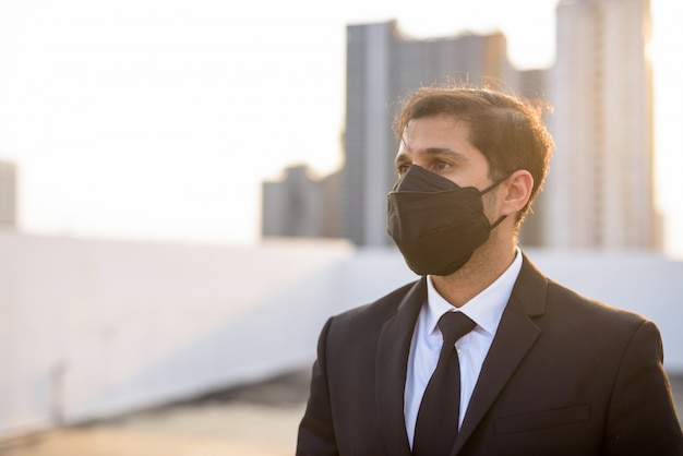 Junger persischer geschäftsmann, der während des tragens der maske zum schutz vor ausbruch und verschmutzung des koronavirus denkt