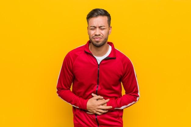 Junger philippinischer fitnessmann krank, leidend unter magenschmerzen, schmerzhaftem krankheitskonzept.