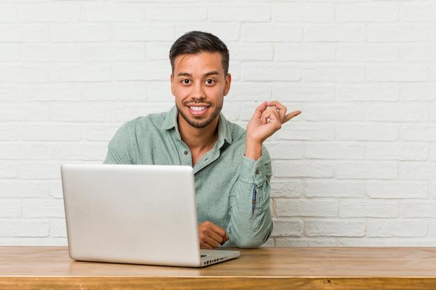 Junger philippinischer mann, der das arbeiten mit seinem laptop lächelt sitzt, freundlich zeigend mit dem zeigefinger weg.