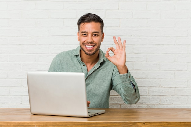 Junger philippinischer mann, der das arbeiten mit seinem laptop nett und überzeugt sitzt, okaygeste zeigend.