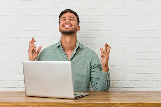 Junger philippinischer mann, der mit seinem laptop arbeitet, der finger kreuzt, um glück zu haben