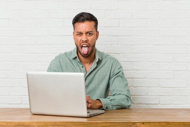 Junger philippinischer mann sitzend, der mit seinem laptop arbeitet, der lustig und freundlich zunge herausstreckt.