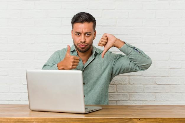 Junger philippinischer mann sitzend, der mit seinem laptop arbeitet, zeigt daumen hoch und daumen runter, schwieriges auswahlkonzept