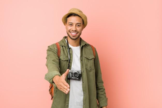 Junger philippinischer reisendmann, der hand an der kamera in der grußgeste ausdehnt.