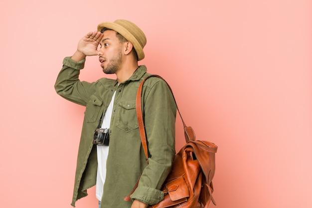 Junger philippinischer reisendmann, der weit weg schaut, hand auf stirn halten.