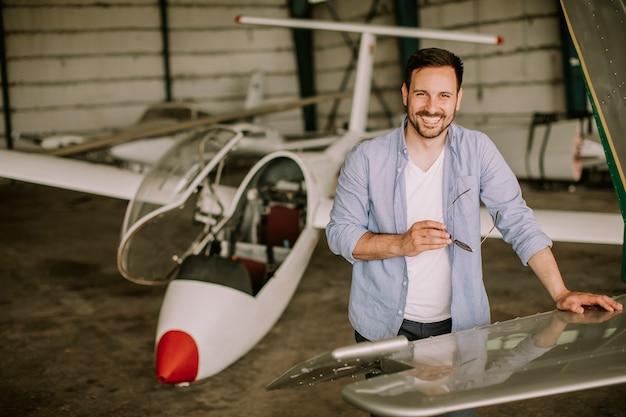Junger pilot, der flugzeug im hangar überprüft
