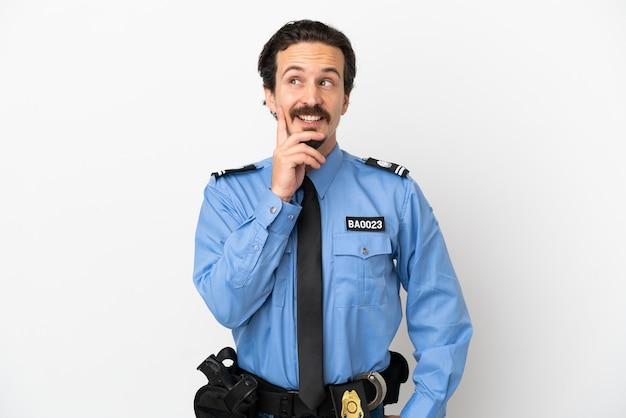 Junger polizist über isoliertem hintergrund weiß beim nachschlagen eine idee denken