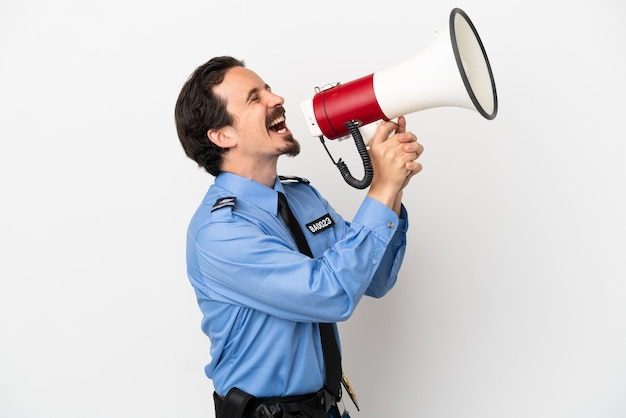 Junger polizist über isoliertem hintergrund weiß, der durch ein megaphon schreit