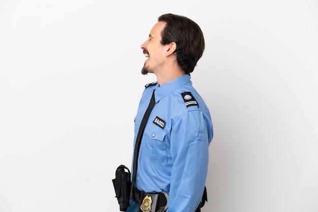 Junger polizist über isoliertem hintergrund weiß lachend in seitenlage