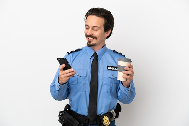 Junger polizist über isoliertem hintergrund weiß mit kaffee zum mitnehmen und einem handy