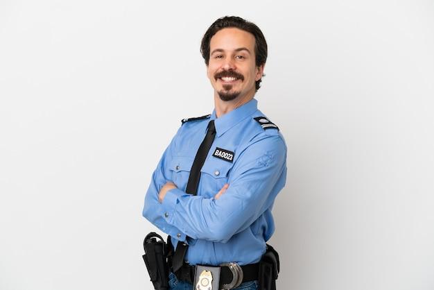 Junger polizist über isoliertem hintergrund weiß mit verschränkten armen und freut sich