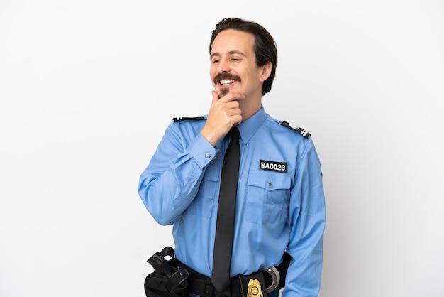 Junger polizist über isoliertem hintergrund weiß zur seite schauend