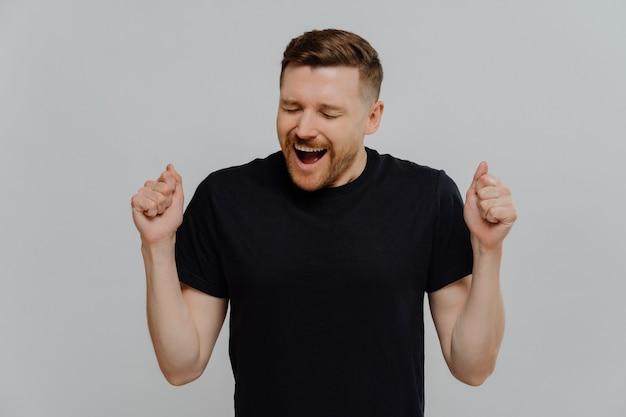 Junger positiv aufgeregter mann in lässigem schwarzem hemd, der fäuste ballt und erfolg mit glücklichem gesichtsausdruck feiert