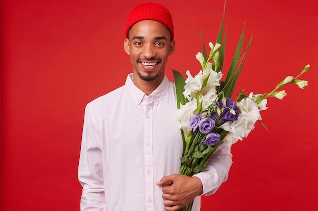 Junger positiver afroamerikaner attraktiver kerl, trägt in weißem hemd und rotem hut, schaut in die kamera und hält blumenstrauß, steht über rotem hintergrund und lächelt.