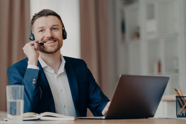 Junger positiver geschäftsmann im anzug, der am tisch im heimbüro sitzt und ein headset trägt, während er eine online-konferenz auf dem laptop organisiert, männlicher freiberufler, der videoanrufe mit dem team hat. remote-work-konzept