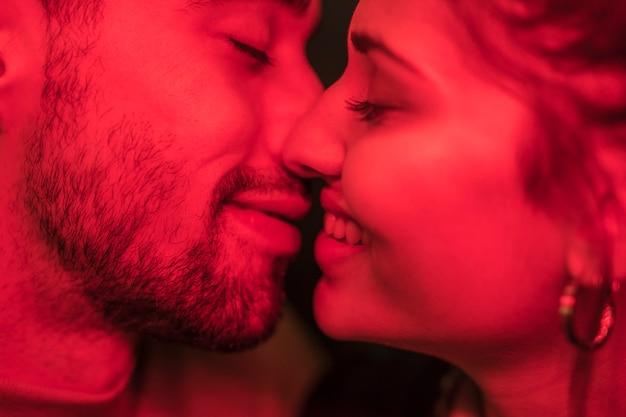 Junger positiver kerl, der lächelnde dame in der rötung küsst