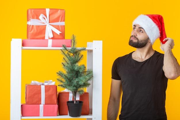 Junger positiver mann mit bart und weihnachtsmann-hut steht in der nähe des standes mit geschenken und weihnachten