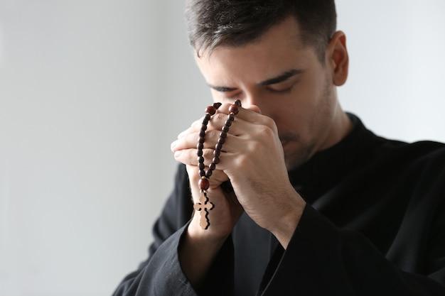 Junger priester mit rosenkranzperlen, die auf lichtraum beten