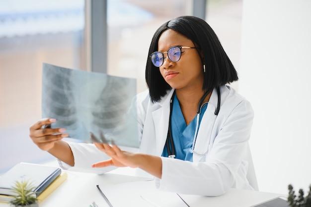 Junger professioneller afroamerikanischer arzt, der röntgenaufnahme der brust des patienten untersucht