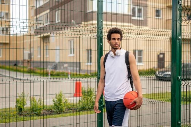 Junger professioneller basketballspieler der gemischten rasse mit ball, der durch zaun des spielplatzes in der städtischen umgebung steht