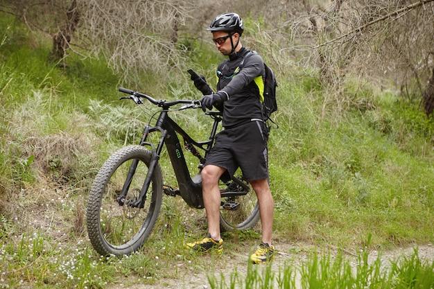 Junger professioneller fahrer gekleidet in fahrradkleidung und schutzausrüstung, die nach gps-koordinaten unter verwendung des navigators auf seinem smartphone sucht, während batteriebetriebenes fahrrad im wald an sonnigem tag fährt