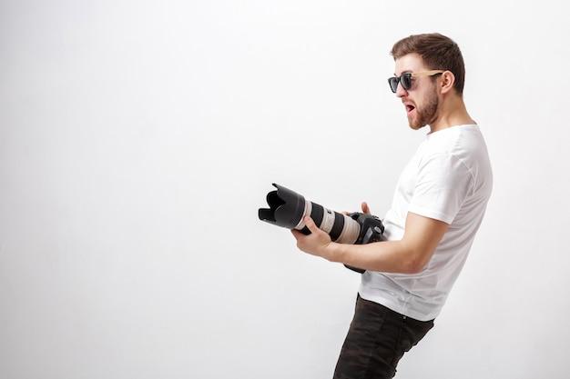 Junger professioneller fotograf in einem weißen hemd, der zum fotografieren bereit ist und eine digitalkamera mit einem langen objektiv verwendet
