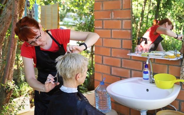 Junger professioneller friseur macht frau vor dem spiegel im hof im freien haarschnitt