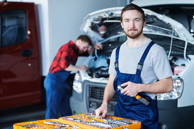 Junger professioneller handwerker in t-shirt und overalls, die sie beim stehen von offenem werkzeugsatz mit instrumenten betrachten