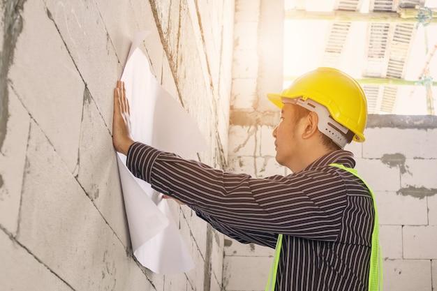 Junger professioneller ingenieurarbeiter im schutzhelm, der an hausbaustelle mit blaupause arbeitet