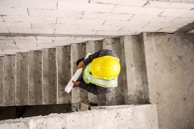 Junger professioneller ingenieurarbeiter im schutzhelm und im blaupausenpapier zur hand auf der baustelle des hauses