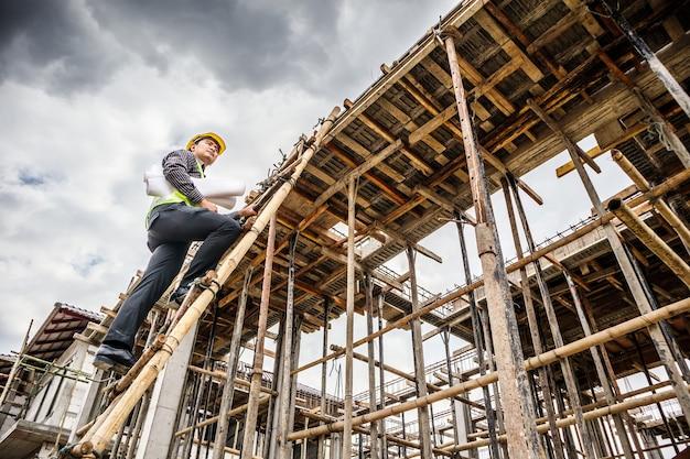 Junger professioneller ingenieurarbeiter im schutzhelm und im blaupausenpapier zur handarbeit auf leiter auf der baustelle des hauses