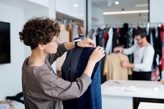 Junger professioneller kleidungsdesigner, der zur schaufensterpuppe steht und über unvollendetem kleid für kunden arbeitet