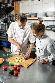Junger professioneller männlicher koch, der seiner weiblichen auszubildenden zeigt, wie man frische zucchini kocht, während beide am tisch in der küche des restaurants stehen?