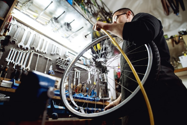 Junger professioneller mann, der vorbereitet, luft in fahrradrad zu pumpen.