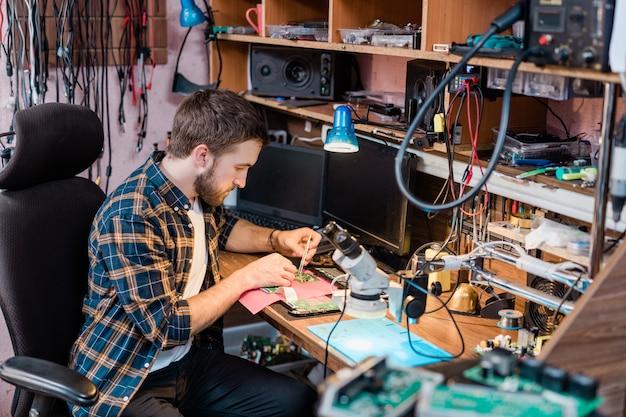 Junger professioneller mechaniker mit einer kleinen stahlpinzette, die in seiner werkstatt ein demontiertes touchpad oder ein anderes gerät repariert