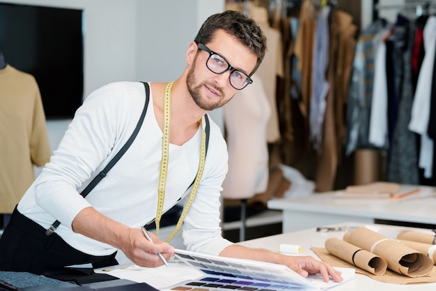 Junger professioneller modedesigner mit maßband, der sie beim vorbereiten der neuen saisonalen kollektion in werkstatt betrachtet