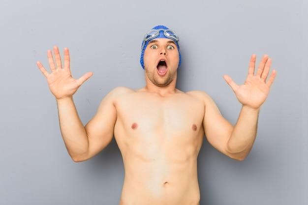 Junger professioneller schwimmermann, der wegen einer drohenden gefahr schockiert wird