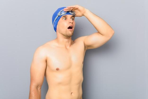 Junger professioneller schwimmermann, der weit weg schaut und hand auf stirn hält.