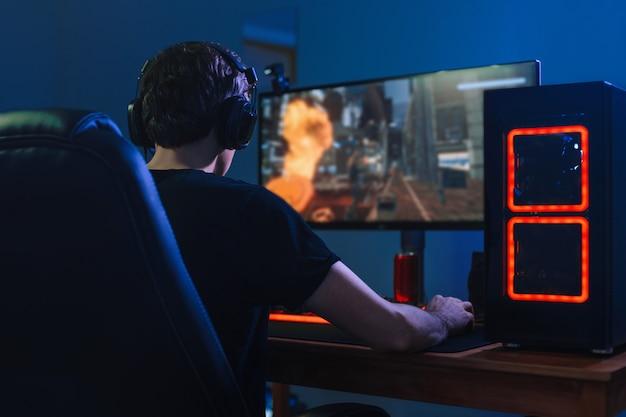 Junger professioneller spieler, der turniere online-videospiele am computer mit kopfhörern in seinem zimmer spielt