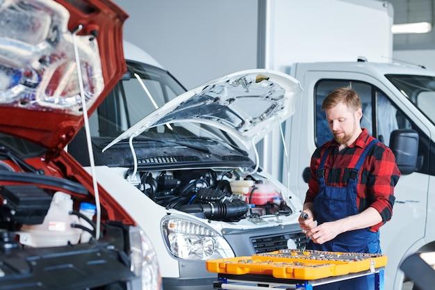Junger professioneller techniker in overalls, die neben dem auto stehen und handwerkzeuge für reparaturarbeiten vorbereiten