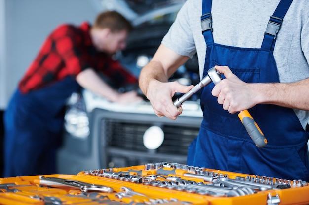 Junger professioneller wartungsserviceingenieur im overall, der handwerkzeug vor der reparatur des autos konstruiert