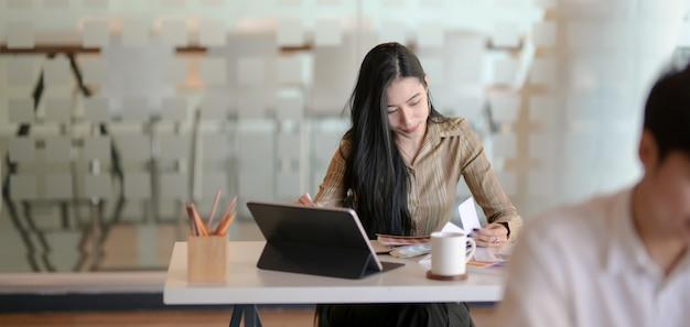 Junger professioneller weiblicher designer, der an seinem projekt im modernen büro arbeitet