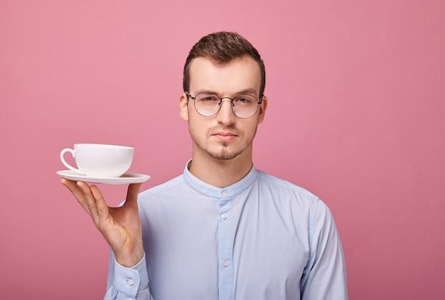 Junger professor in den gläsern, die nach der arbeit bei einem weißen becher kaffee in seiner hand liegen